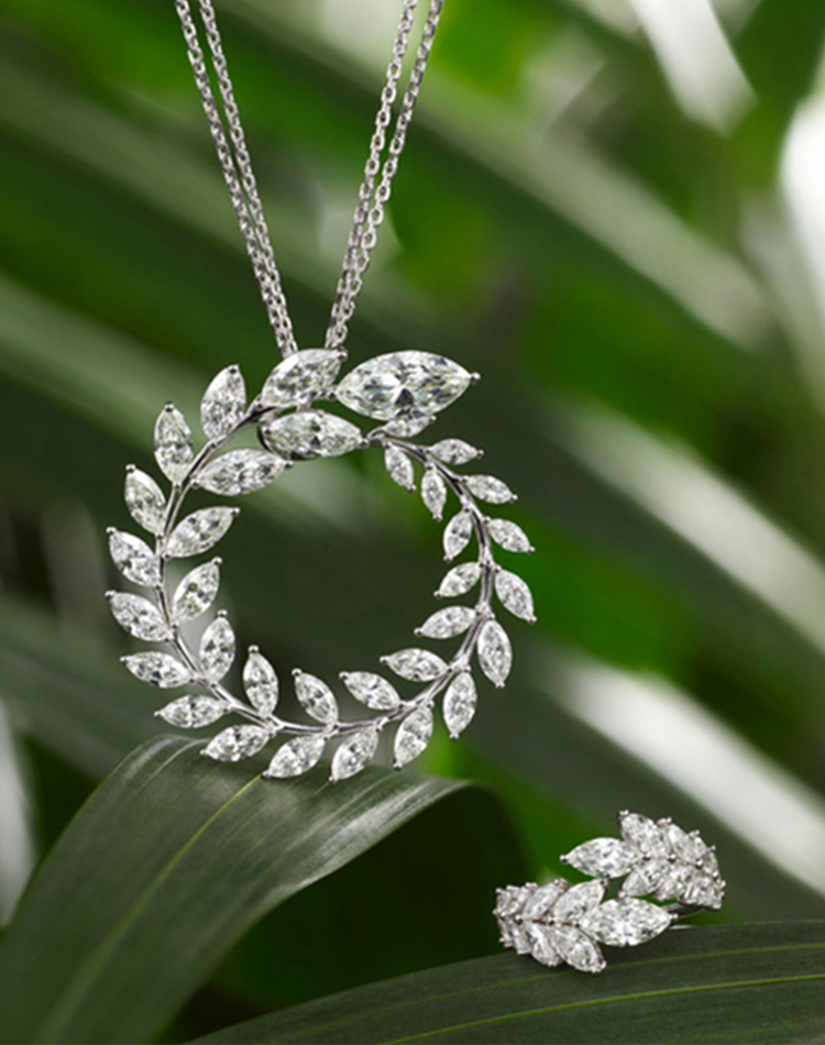 Close-up image a green carpet collection diamond pendant and ring with green leaves