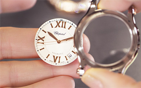image of hand holding dial of watch outside of the watch case