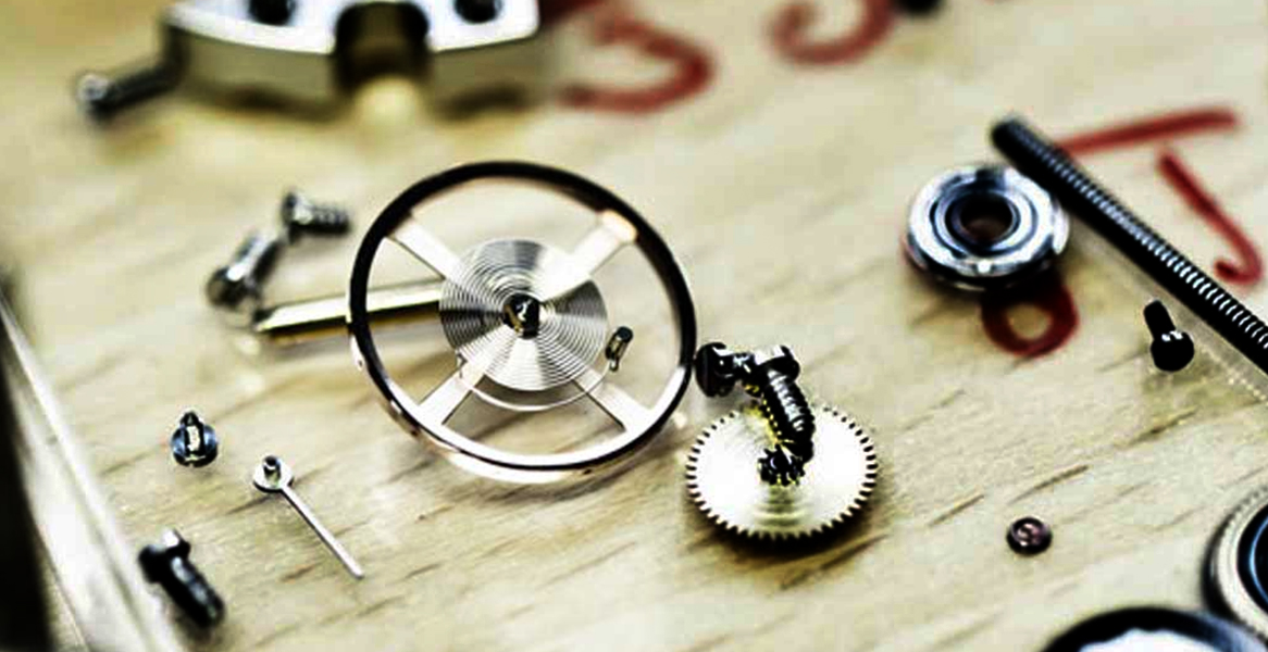 image of parts of a watch movement on wood