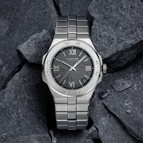 A silvery Alpine Eagle watch over dark rocks, with a dark grey dial reminiscing of an eagle's iris.