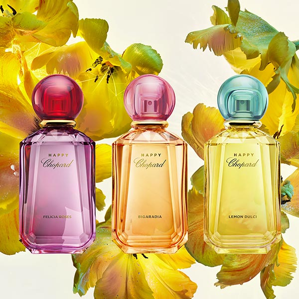 Three colorful Happy Chopard fragrances (Felicia Roses, Bigaradia and Lemon Dulci) over a background of yellow flowers.