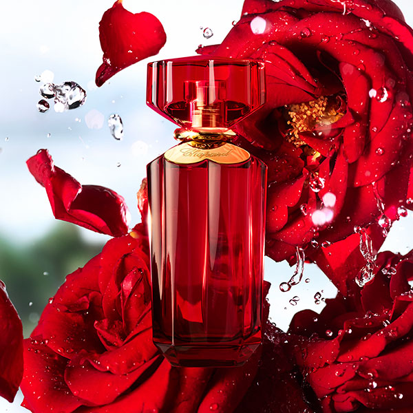 The new Chopard Love fragrance in its red bottle, with red roses and drops of water in the background.