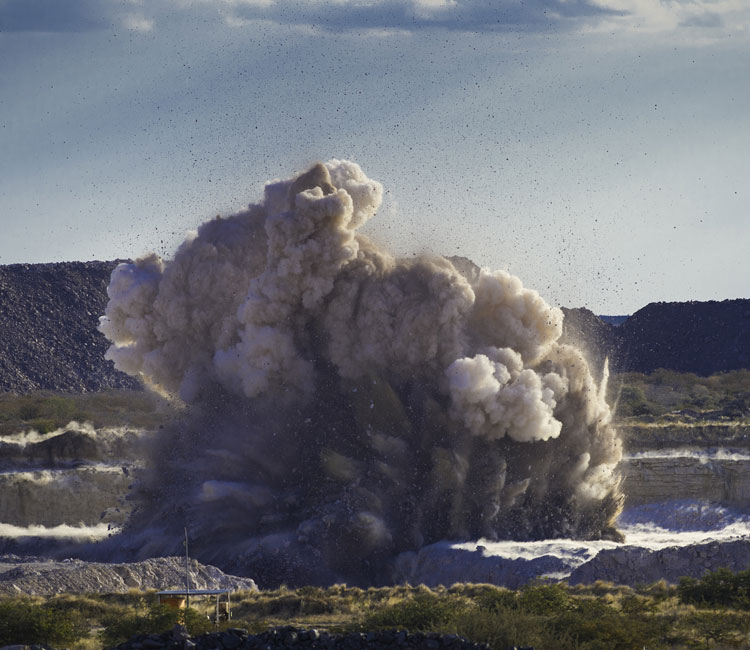 Image of controlled explosion at Diamond quarry in desert landscape