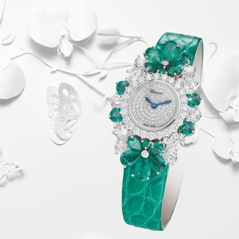 Image of Diamond and emerald watch with green alligator strap set over white paper cut out scene of butterflies and flowers