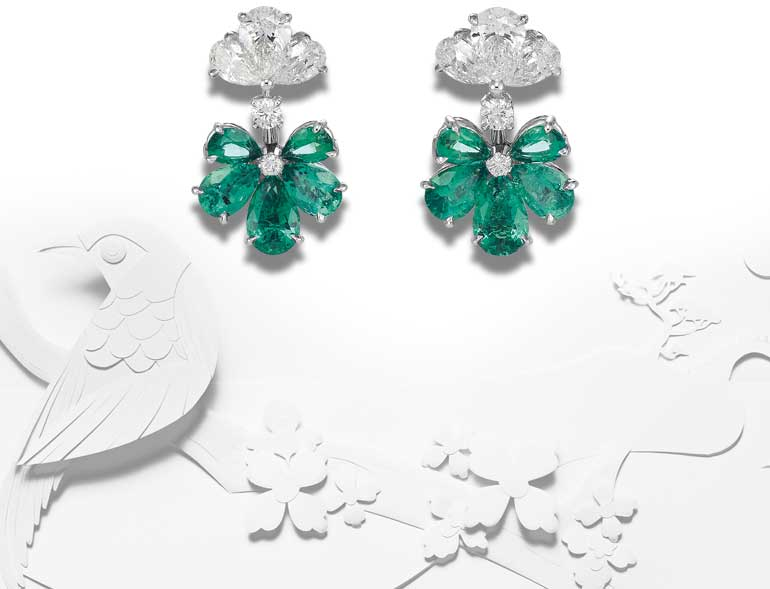 Image of Diamond and emerald earrings set over white paper cut out scene of birds and flowers
