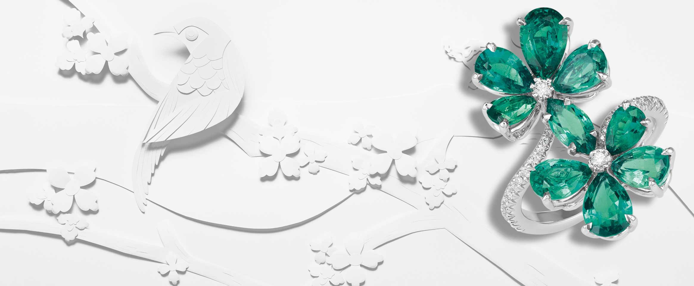 Image of Diamond and emerald ring set over a white paper cut out scene with birds and flowers