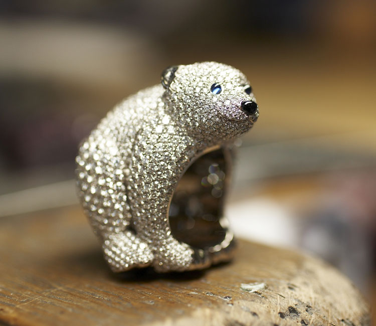 Close-up image of diamond paved Polar bear ring on wooden block