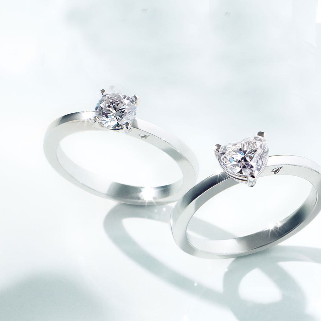 close-up view of 2 platinum solitaires engagement rings with 2 different diamond cuts, round and heart