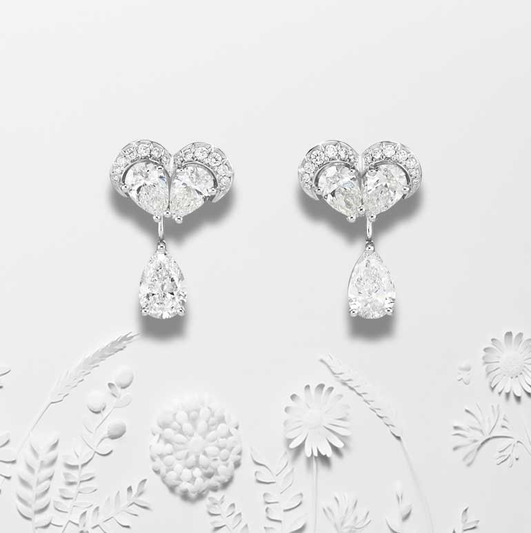 Close-up view of Green carpet collection Diamond earrings over white paper cut out scene of plants