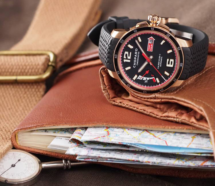 Image of a Chopard mille miglia rose gold watch on a rubber strap placed over a leather notebook