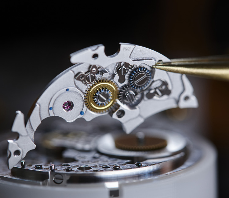 Close-up image of a watchmaker lifting a watch movement with Tweezers