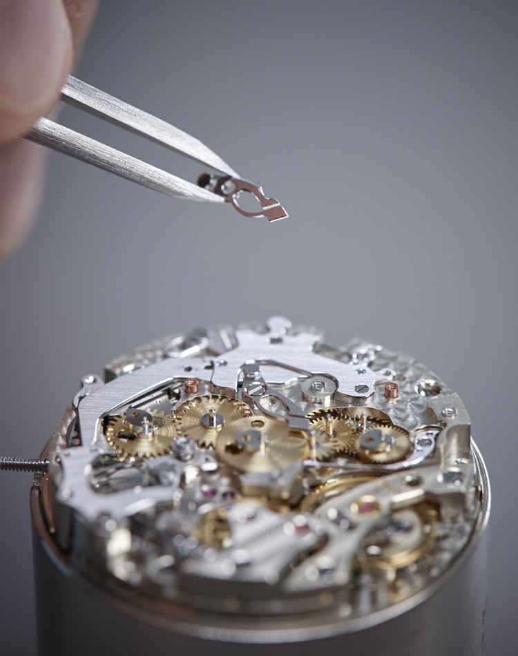 Close-up Image of a watchmaker placing a part in a movement with tweezers