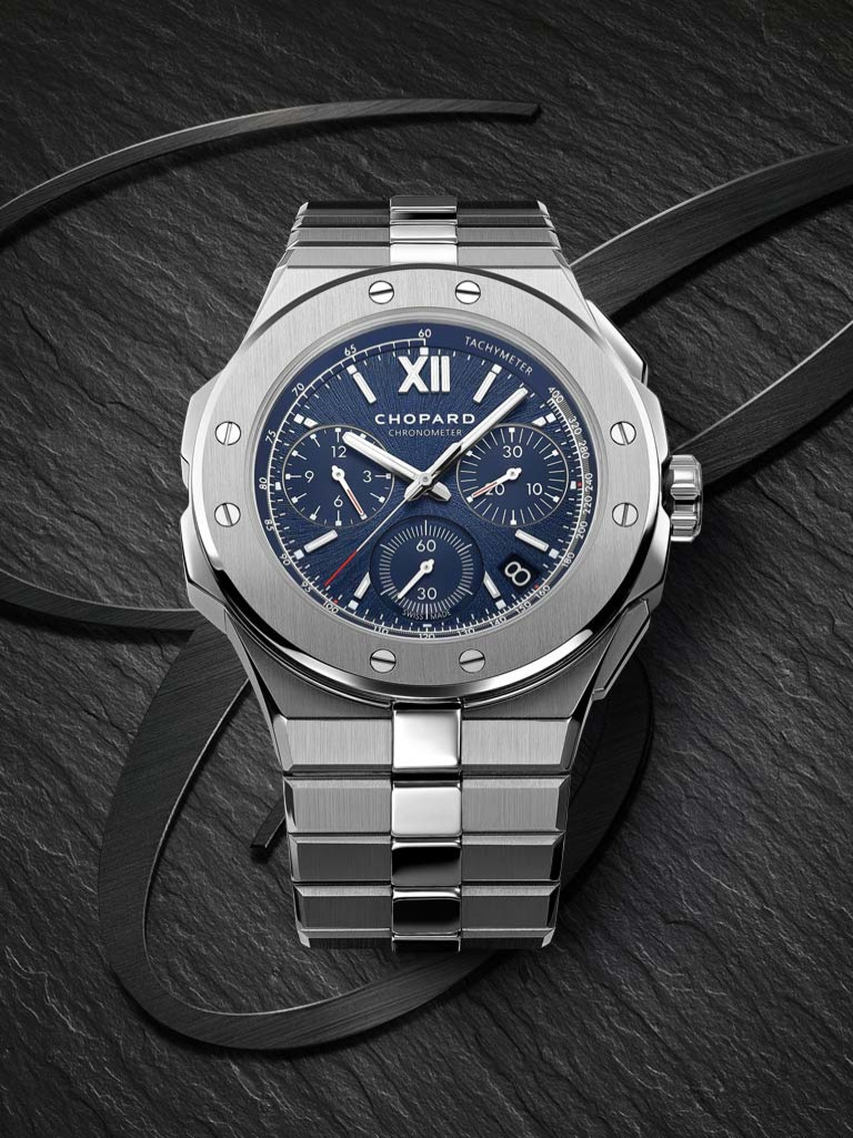 Stainless steel chronograph watch with blue dial on gray background