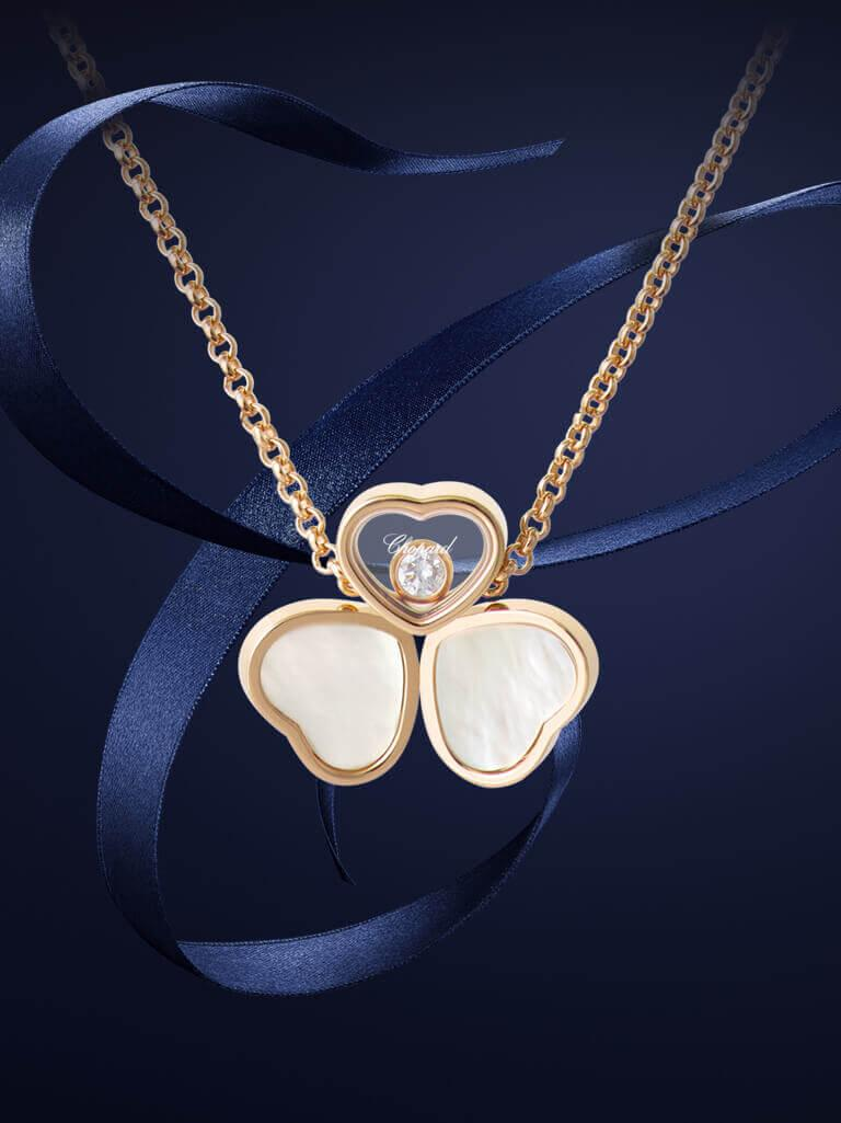 A Happy Heart's Necklace made of 3 rose gold hearts, the two bottom ones with a nacre case and the top one with a diamond.