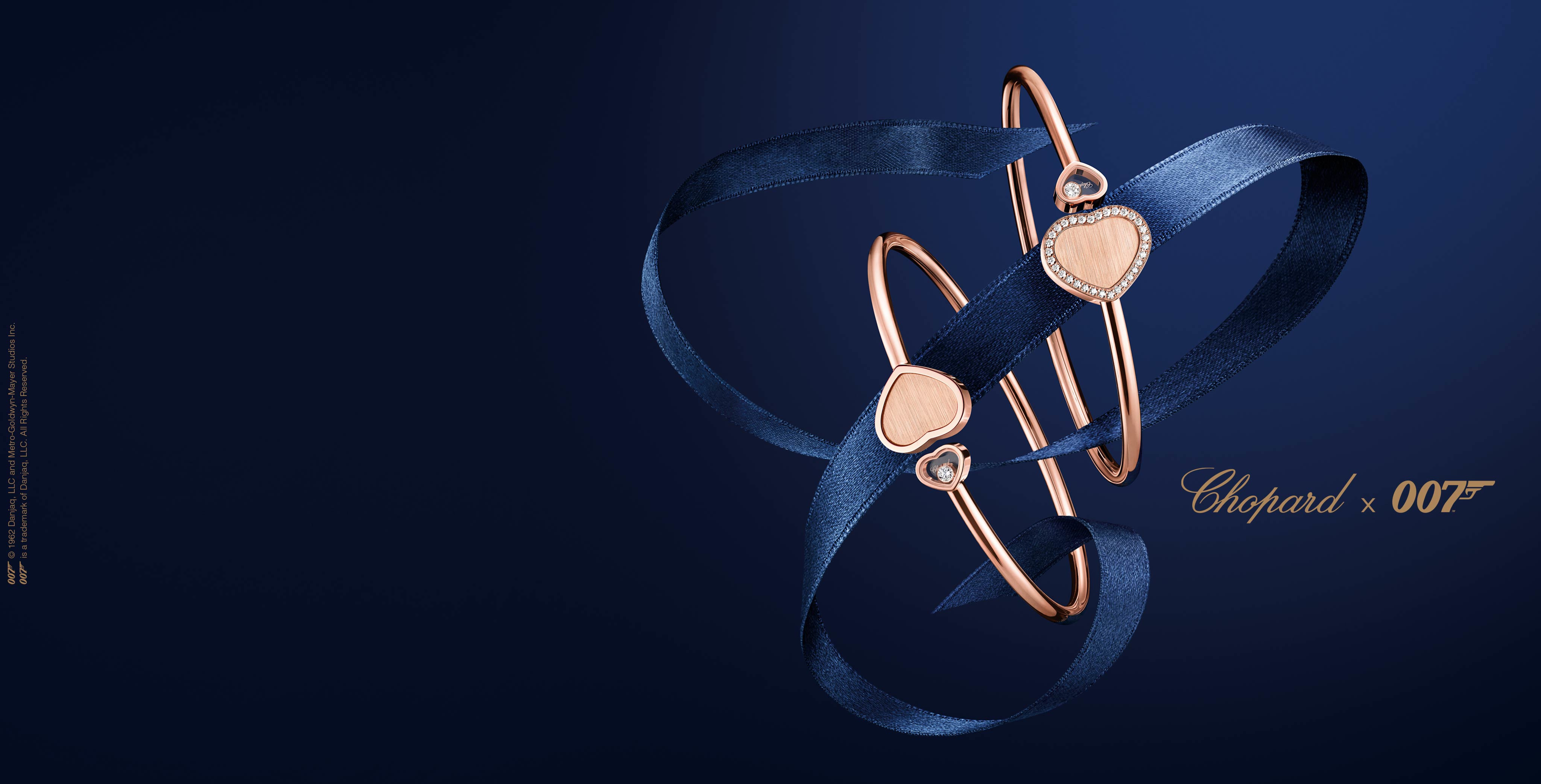 Two Golden Hearts bracelets entangled in a ribbon forming the famous C from Chopard, over a dark blue background.