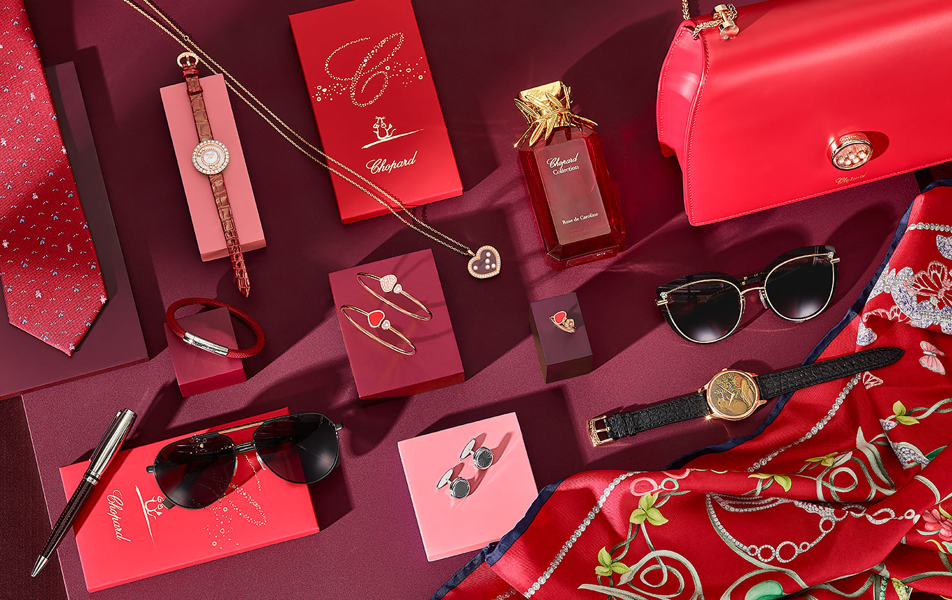 Several Chopard products (jewels, perfumes, handbags, the year of the rat Urushi watch) with red hues over a red background.